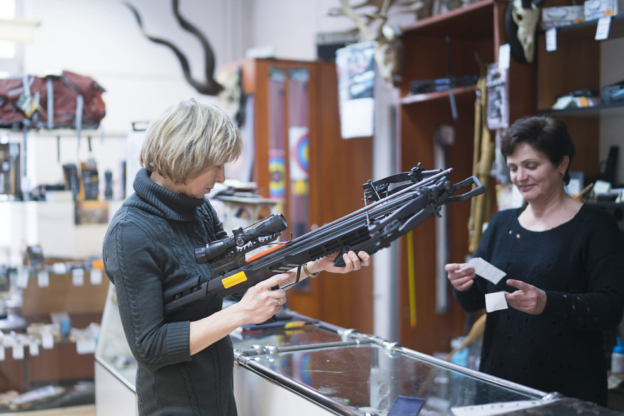 The attractive blonde mature, 50-years-old woman examining the crossbow in the small hunting store, with assistance of the woman - salespersone. Kaliningrad, Russia, Eastern Europe.